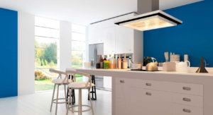 Cocina con isla dos taburetes ventana con paso de luz natural y elementos de cocinar sobre la encimera