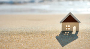 Fachada de una casa hecha en cartón sobre la arena de fondo vista difuminada del mar