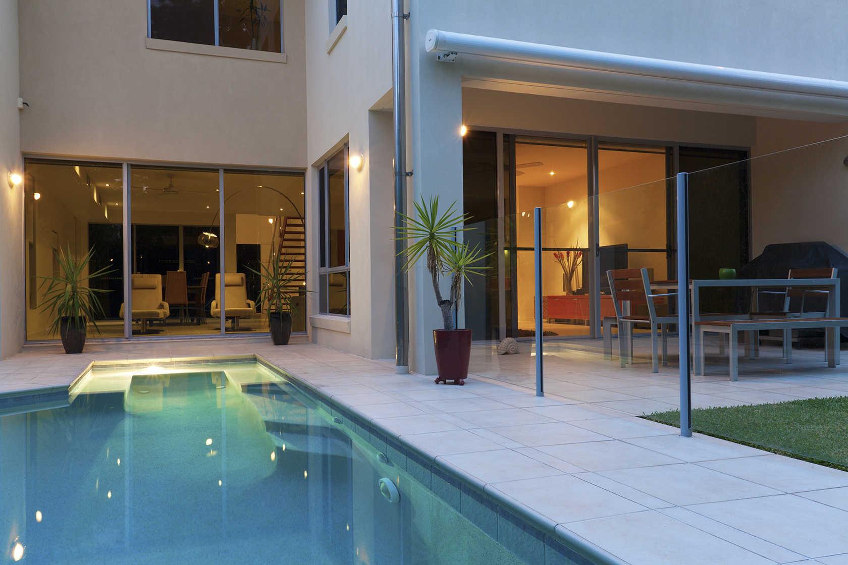 Entrada de Casa moderna de grandes ventanas piscina iluminada