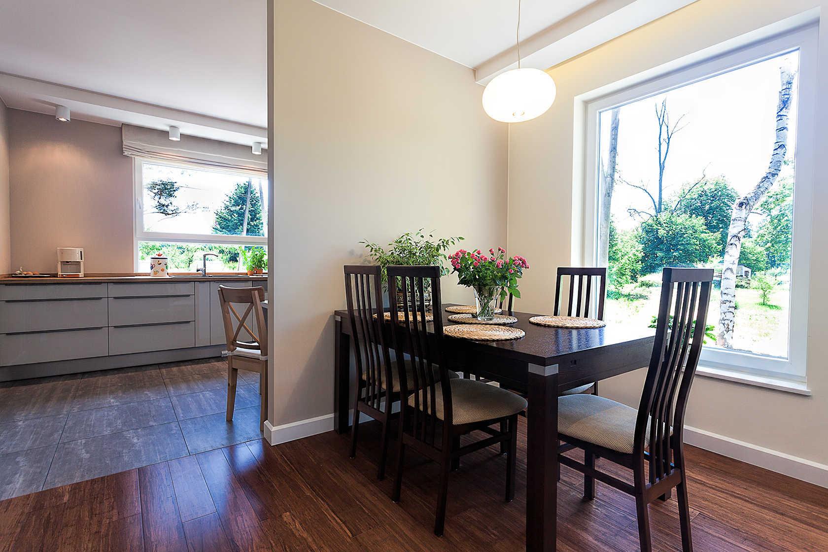 Mesa con cuatro sillas piso de parque vista de la cocina ventanas hacia en jardín