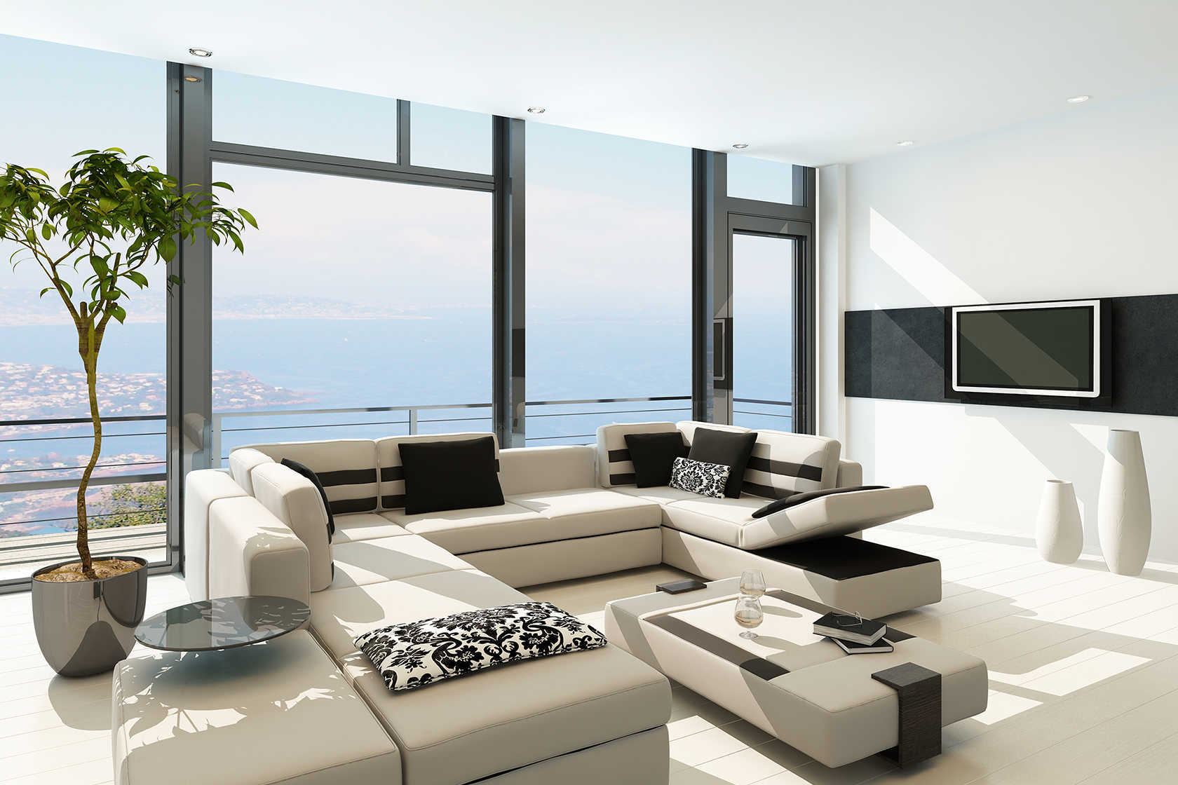 Salón minimalista sofá blanco pared de cristal con vistas al mar