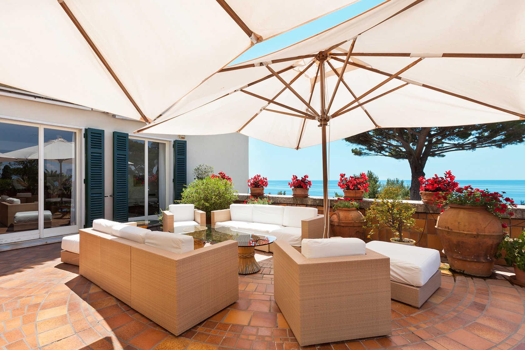 Terraza con sofás blancos y sombrillas jardineras con flores y vistas al mar