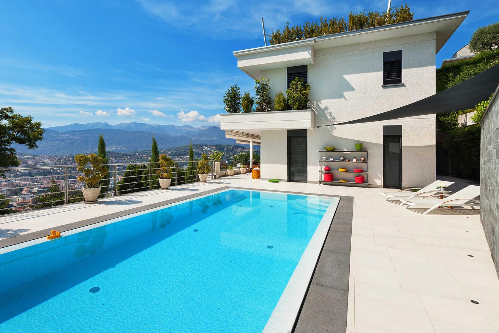 Gran piscina rectangular dos tumbonas y vivienda de fondo
