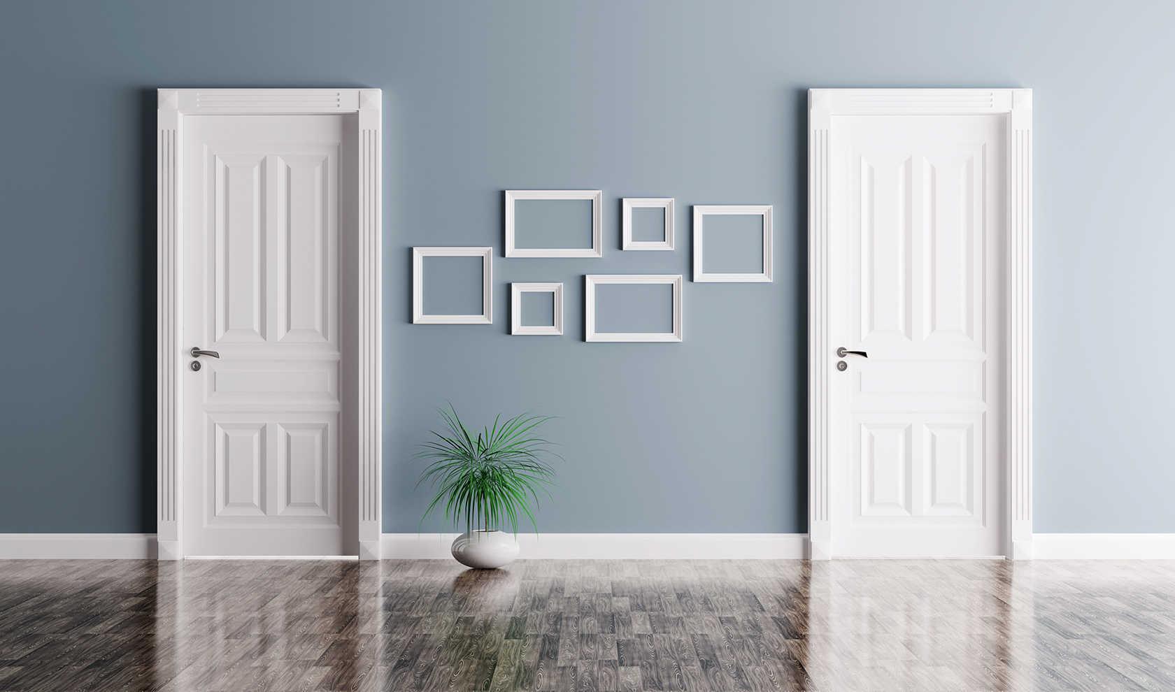 Dos puertas blancas separadas por marcos vacíos colgados en la pared suelo de madera colores marrones