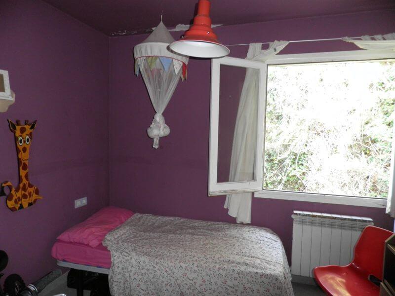 Ático Dúplex Arenys de Mar Habitación con ventana abierta, cama y muebles