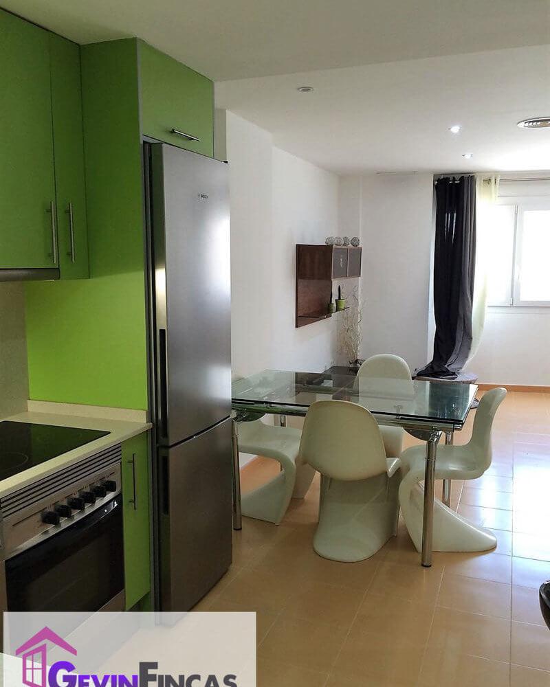 Salón con mesa y sillas y vista de la cocina de Loft en alquiler Canet de Mar