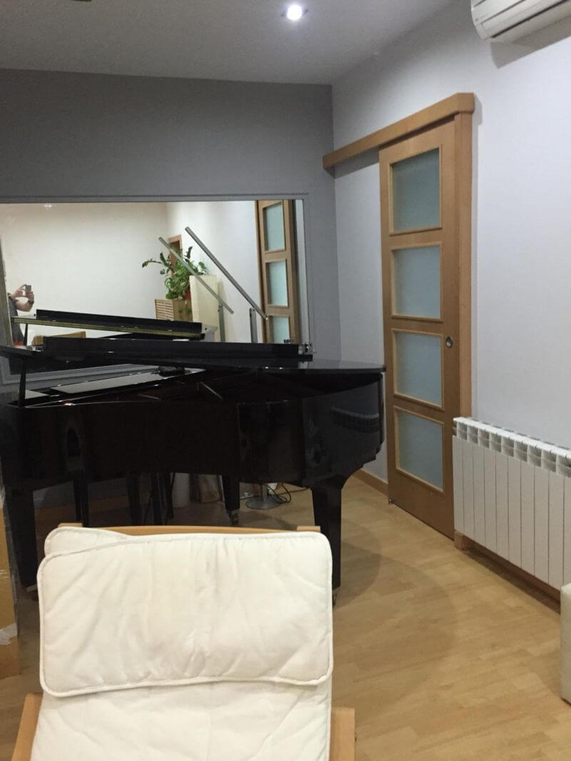 Salón con piano sofá y calefacción de piso en venta en barrio Eixample de Barcelona