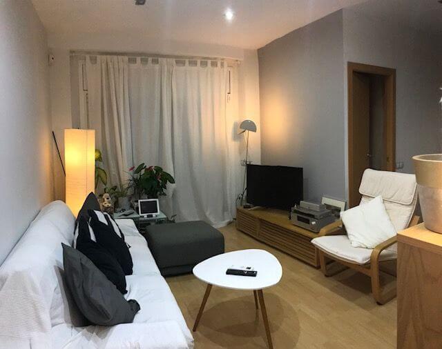 Salón elegante con sillones muebles, televisor de piso en venta en barrio Eixample de Barcelona