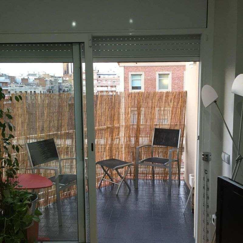 Ventana grande con salida a terraza con mesas y sillas de piso en venta en Eixample de Barcelona