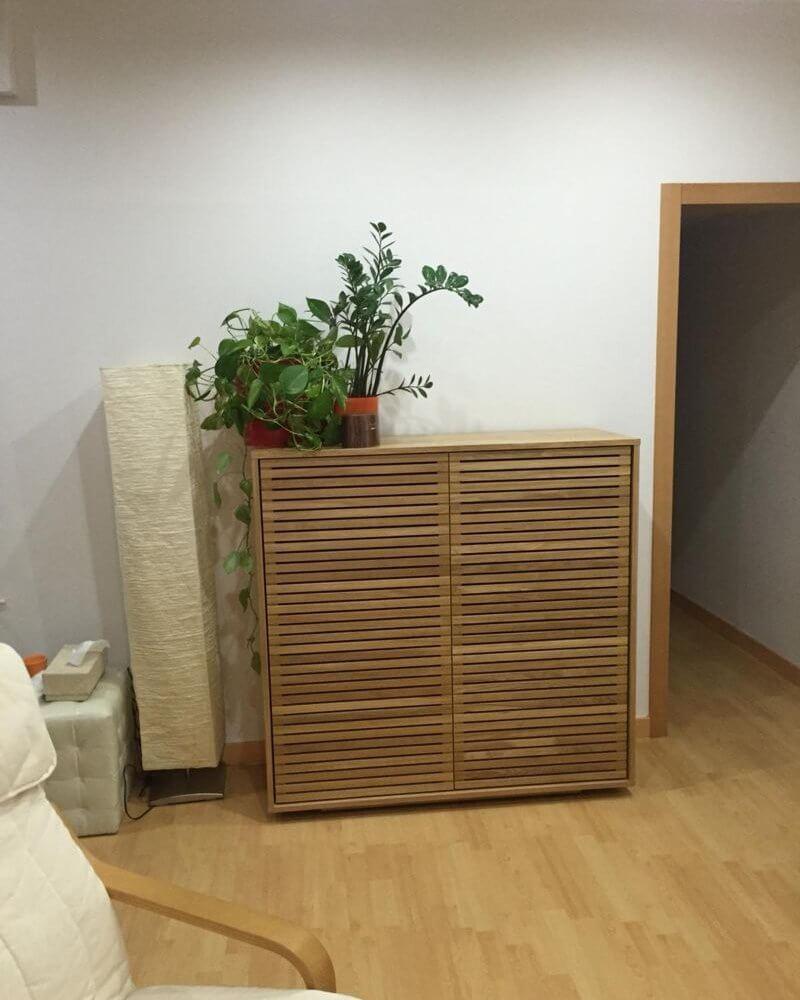 Parte de sal´´on con mueble de madera sillón y suelo de parqué de piso a la venta en barrio Eixample de Barcelona